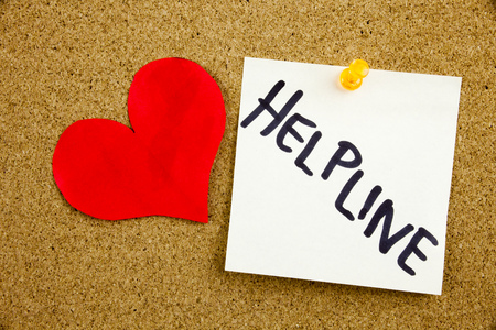 Phrase HELP LINE HELP LINE in black ext on a sticky note pinned to a cork notice board