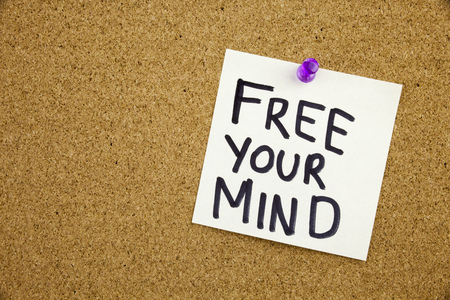 A yellow sticky note writing, caption, inscription Free Your Mind message in black ext on a sticky note
