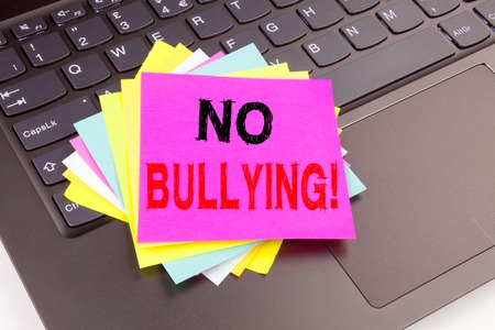 Writing text showing No Bullying made in the office with surroundings such as laptop, marker, pen.