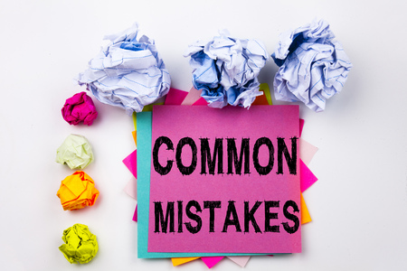 Writing text showing Common Mistakes written on sticky note in office with screw paper balls. Business concept for Common Decision Mistakes on the isolated background.