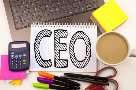 Word writing CEO in the office with laptop, marker, pen, stationery, coffee. Business concept for Operating Leader Business Executive President Workshop white background with space