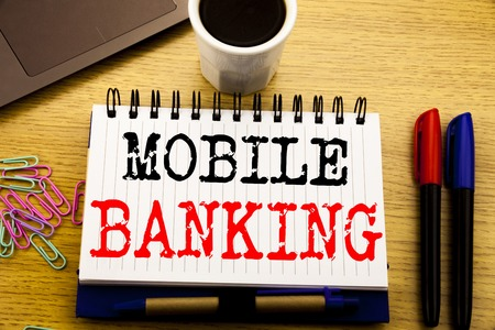 Hand writing text caption showing Mobile Banking. Business concept for Internet Banking e-bank written on notebook on the wooden background in the Office with laptop coffee