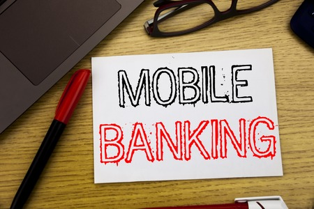 Handwriting Announcement text showing Mobile Banking. Business concept for Internet Banking e-bank written on paper, wooden background in office copy space, marker pen and glasses