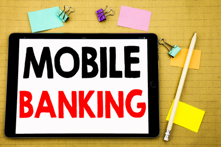 Hand writing text caption inspiration showing Mobile Banking. Business concept for Internet Banking e-bank Written on tablet, wooden background with sticky note and pen