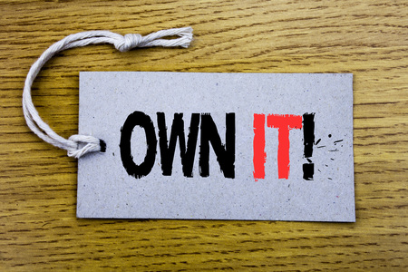 Photo pour Conceptual hand writing text caption showing Own It Exclamation. Business concept for Ownership Control written on price tag paper with copy space on wooden vintage background - image libre de droit