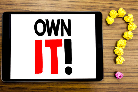 Writing text showing Own It Exclamation. Business concept for Ownership Control written on tablet computer on wooden background with question mark made of folded paper.