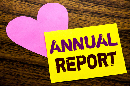 Hand writing text caption inspiration showing Annual Report. Business concept for Analyzing Performance  written on sticky note paper, wooden background. With pink heart meaning love adoration.