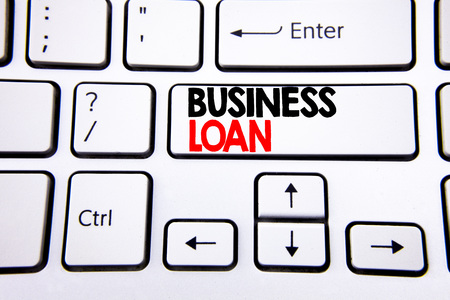 Hand writing text caption inspiration showing Business Loan. Business concept for Lending Finance Credit written on white keyboard key with copy space. Top view