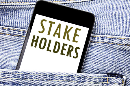 Handwriting Announcement text showing Stake Holders. Business concept for Stakeholder Engagement Written phone mobile phone, cellphone placed in man front jeans pocket.