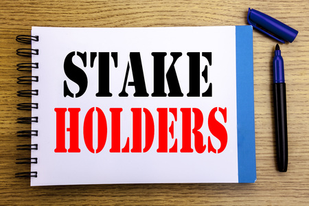 Handwriting Announcement text showing Stake Holders. Business concept for Stakeholder Engagement Written on notepad paper background with space office view with pencil marker