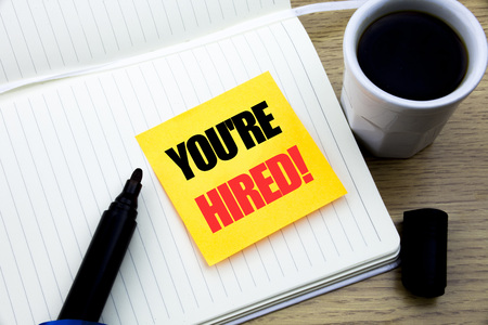 Hand writing text caption inspiration showing You Are Hired. Business concept for Hiring Employee Worker written sticky note paper, Wooden background with copy space, Coffee and marker