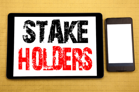 Hand writing text caption inspiration showing Stake Holders. Business concept for Stakeholder Engagement Written on tablet, wooden background with sticky note and pen