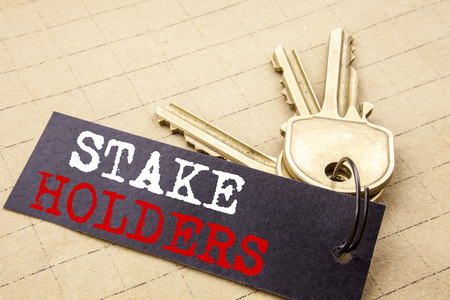 Conceptual hand writing text caption showing Stake Holders. Business concept for Stakeholder Engagement written on note paper attached to keys note paper on the texture background.