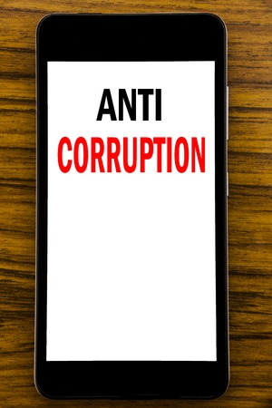 Handwriting Announcement text showing Anti Corruption. Business concept for Bribery Corrupt Text Written on mobile cellphone with wooden background with space on the table