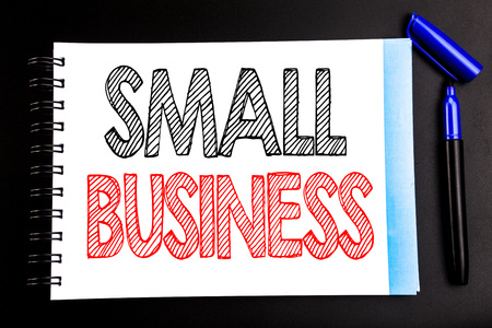 Handwritten text showing Small Business. Business concept writing for Strategy Management Written on notepad paper, black background with space office view with pencil marker