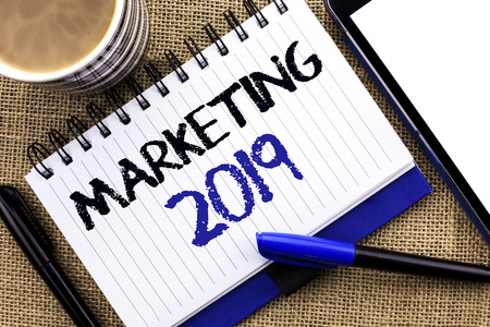 Text sign showing Marketing 2019. Conceptual photo New Year Market Strategies Fresh start Advertising Ideas written Notebook Book the jute background Tablet Coffee Cup and Pens next to it