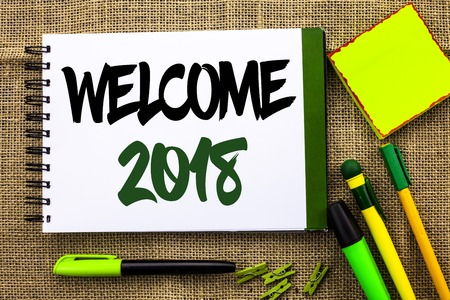 Text sign showing Welcome 2018. Conceptual photo Celebration New Celebrate Future Wishes Gratifying Wish written Notebooke Book the jute background Pens Clips Sticky Note next to it.