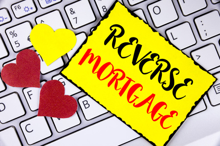 Writing note showing  Reverse Mortgage. Business photo showcasing Elderly homeowner retirement option regular payment benefit written Yellow Sticky Note Paper placed Laptop Hearts next to it.