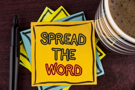 Foto de Writing note showing  Spread The Word. Business photo showcasing Run advertisements to increase store sales many fold written Sticky Note paper Wooden background Coffee Cup and Marker - Imagen libre de derechos