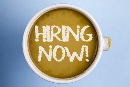 Text sign showing Hiring Now Motivational Call. Conceptual photo Workforce Wanted New Employees Recruitment written Coffee in a broken cup the plain background.