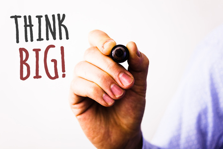 Conceptual hand writing showing Think Big Motivational Call. Business photo texts Have great ideas Dream of something amazingMan holding pen pointing idea message black red letters white background