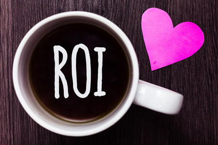 Handwriting text Roi. Concept meaning Return on investment performance measure gains business growth Mug coffee lovely thoughts ideas love hart romantic memories brown wood