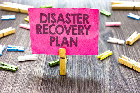 Photo for Writing note showing Disaster Recovery Plan. Business photo showcasing having backup measures against dangerous situation Multiple clips woody table small card clipped notice announcement - Royalty Free Image