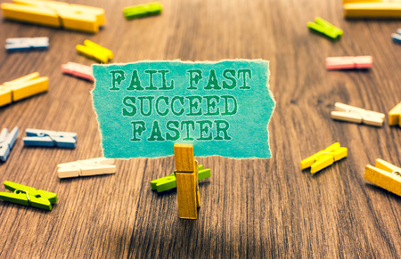 Word writing text Fail Fast Succeed Faster. Business concept for dont give up keep working on it to achieve Clothespin holding turquoise paper note several clothespins wooden floor