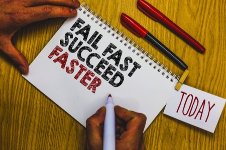 Writing note showing Fail Fast Succeed Faster. Business photo showcasing dont give up keep working on it to achieve Man holding marker notebook clothepin reminder wooden table cup coffee