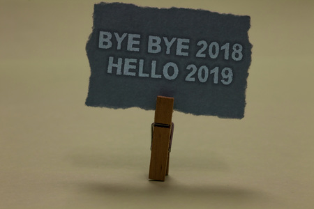 Photo pour Handwriting text writing Bye Bye 2018 Hello 2019. Concept meaning Starting new year Motivational message 2018 is over Paperclip retain ash color written torn thick page on shadow ash floor - image libre de droit