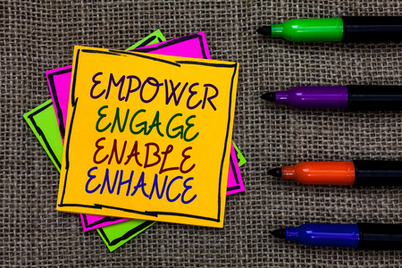 Text sign showing Empower Engage Enable Enhance. Conceptual photo Empowerment Leadership Motivation Engagement Written on some colorful sticky note 4 pens laid in rank on jute base