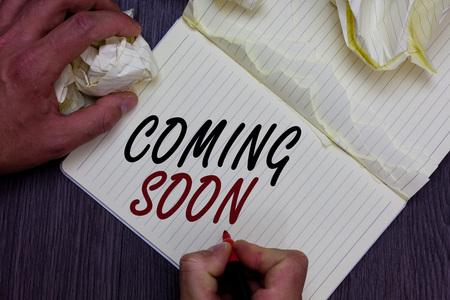 Word writing text Coming Soon. Business concept for something is going to happen in really short time of period Man holding marker notebook crumpled papers ripped pages mistakes made