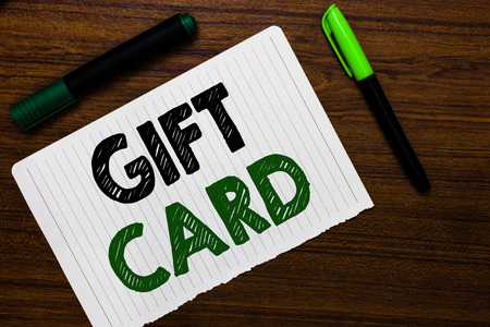 Gift Card message written on paper with markers on wooden background