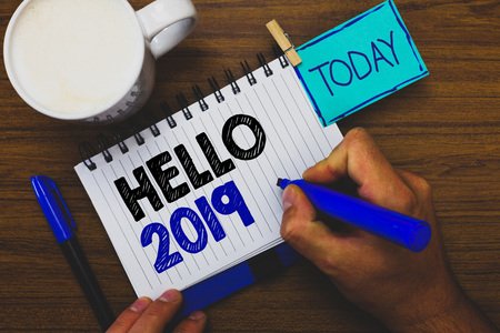 Word writing text Hello 2019. Business concept for Hoping for a greatness to happen for the coming new year Man holding marker notebook clothespin reminder wooden table cup coffee