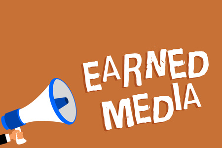 Text sign showing Earned Media. Conceptual photo Publicity gained through promotional efforts by multimedia Man holding megaphone loudspeaker orange background message speaking loud