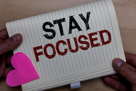 Word writing text Stay Focused. Business concept for Be attentive Concentrate Prioritize the task Avoid distractions Man holding notebook paper heart Romantic ideas messages Wooden background