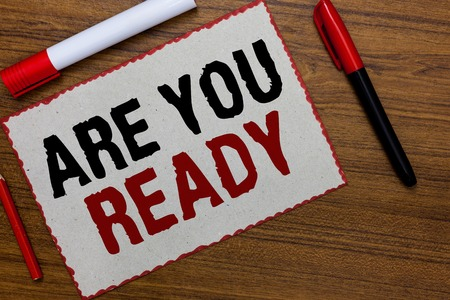 Text sign showing Are You Ready. Conceptual photo Alertness Preparedness Urgency Game Start Hurry Wide awake White paper red borders markers wooden background communicating ideas