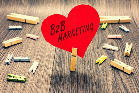 Word writing text B2B Marketing. Business concept for Partnership Companies Supply Chain Merger Leads Resell Clothespin holding red paper heart several clothespins wooden floor romance
