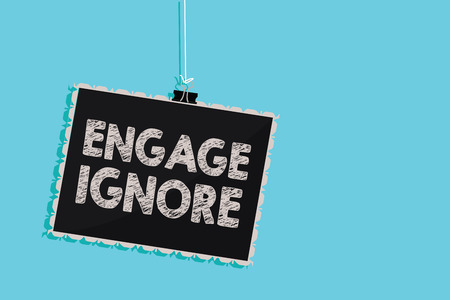 Photo pour Conceptual hand writing showing Engage Ignore. Business photo showcasing Silent Treatment Manipulative Punishment Sulking Shunning Hanging blackboard message information sign blue background - image libre de droit