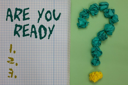 Text sign showing Are You Ready. Conceptual photo Alertness Preparedness Urgency Game Start Hurry Wide awake Notebook paper crumpled papers forming question mark green background