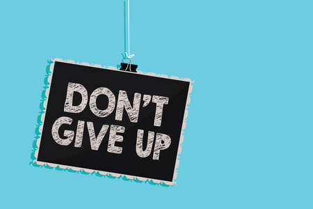 Conceptual hand writing showing Don t not Give Up. Business photo showcasing Determined Persevering Continue to Believe in Yourself Hanging blackboard message information sign blue background