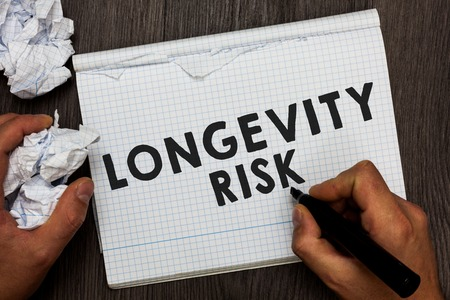 Writing note showing Longevity Risk. Business photo showcasing Potential threat due to increasing lifespan of pensioners Man holding marker notebook crumpled papers several tries made