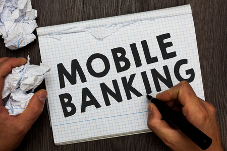 Writing note showing Mobile Banking. Business photo showcasing Monitoring account balances Transferring funds Bill payment Man holding marker notebook crumpled papers several tries made
