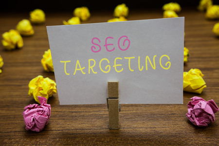 Handwriting text writing Seo Targeting. Concept meaning Specific Keywords for Location Landing Page Top Domain Clothespin holding white paper note crumpled papers several tries mistakes