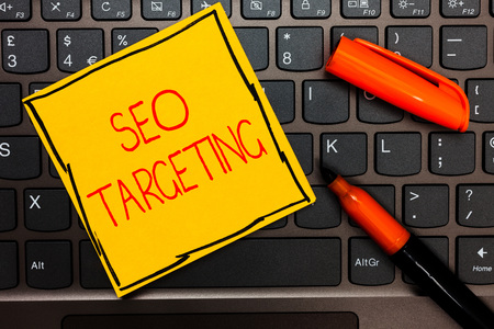 Writing note showing Seo Targeting. Business photo showcasing Specific Keywords for Location Landing Page Top Domain Yellow paper keyboard Inspiration communicate ideas orange markers