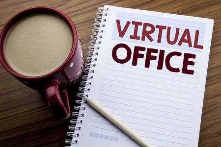 Hand writing text caption inspiration showing Virtual Office. Business concept for Online Way Of Working written on note paper notepad on the wooden background with coffee and pen.
