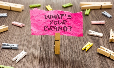 Photo pour Conceptual hand writing showing What s is Your Brand question. Business photo showcasing Define Individual trademark Identify Company Paperclip hold pink note with texts many clips wooden floor - image libre de droit