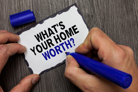 Foto für Handwriting text What s is Your Home Worth question. Concept meaning Value of a house Property Cost Price Rate Gray wooden deck hand hold black marker written black lined sticky note - Lizenzfreies Bild