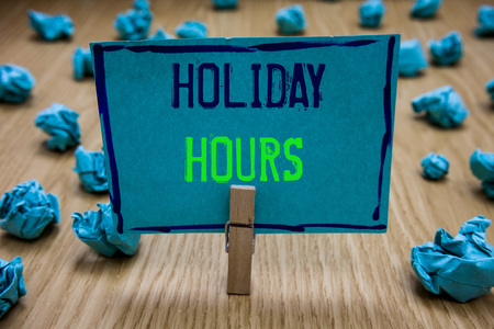 Handwriting text writing Holiday Hours. Concept meaning Schedule 24 or 7 Half Day Today Last Minute Late Closing Clothespin holding blue paper note crumpled papers several tries mistakes
