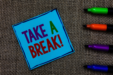 Photo pour Writing note showing Take A Break. Business photo showcasing Resting Stop doing something recreation time get out of work Blue paper on written letters besides color pens on black sack - image libre de droit